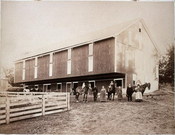 Black and white image of Farmer and wife each holding horses by their reins. To the left is the white farmhouse with a porch and slate roof. The barn and outer building is behind the farmer. The outhouse is behind his wife.